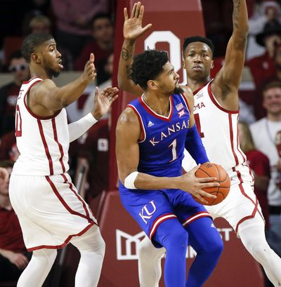 Kansas forward Dedric Lawson, center, tries to get to the basket between Oklahoma guard Christian James, left, and forward Kristian Doolittle, right, in the second half of an NCAA college basketball game in Norman, Okla., Tuesday, March 5, 2019. Oklahoma won 81-68. (Nate Billings / Associated Press)
