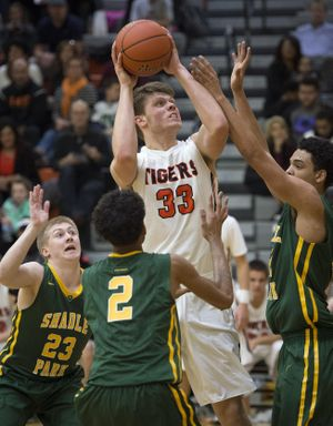 Lewis and Clark's Vaughnden Handel (33) looks to the basket as Shadle Park's (left to right) Cole Riblet (23) Jakobe Ford (2) and Kobe Reese defend during the second half of a boy's high school basketball game, Friday., Jan. 15, 2016, at Lewis and Clark High School. (Colin Mulvany / The Spokesman-Review)