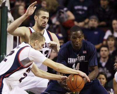 Gonzaga guard Micah Downs, left, steals the ball from Connecticut center Hasheem Thabeet, of Tanzania, right, as Gonzaga's Josh Heytvelt, second from left, looks on in the first half of an NCAA college basketball game Saturday at KeyArena in Seattle.  (The Associated Press)