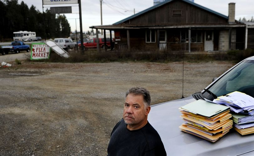 Developer Alan Johnson stands with stacks of documents from a lawsuit against him at the intersection of highways 95 and 54 in Athol. A fight with the Idaho Transportation Department has held up development of a travel center, grocery store and hotel on the site. (Kathy Plonka)