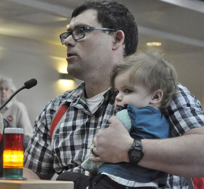 """–  Tim Moses, of Tumwater, Wash., holds his 1 year-old daughter Lily as he testifies in favor of a bill to require secure storage of firearms in the home. Moses said he can get to his locked firearms in four seconds and """"if I need my gun faster than that, I wear it."""" (Jim Camden / The Spokesman-Review)"""