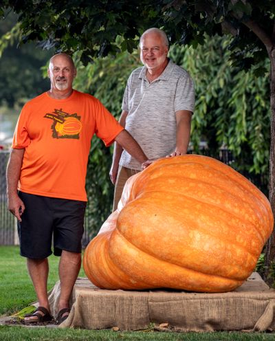 Gerry Klumb, left, grew the biggest pumpkin (over 800 pounds) entered into this year's Spokane County Interstate Fair, while his neighbor, Greg Johnson, also grew a large pumpkin fair entry.  (Colin Mulvany/THE SPOKESMAN-REVIEW)