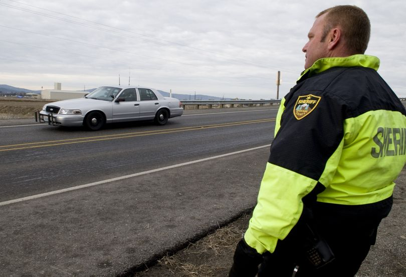 Sheriff's Deputy Craig Chamberlin monitors how well a test car brakes after an  application of liquid de-icer near the intersection of  Wellesley and Trent avenues Jan. 29, during the reconstruction of an accident that  injured two East Valley High students Dec. 29.colinm@spokesman.com (Colin Mulvany)