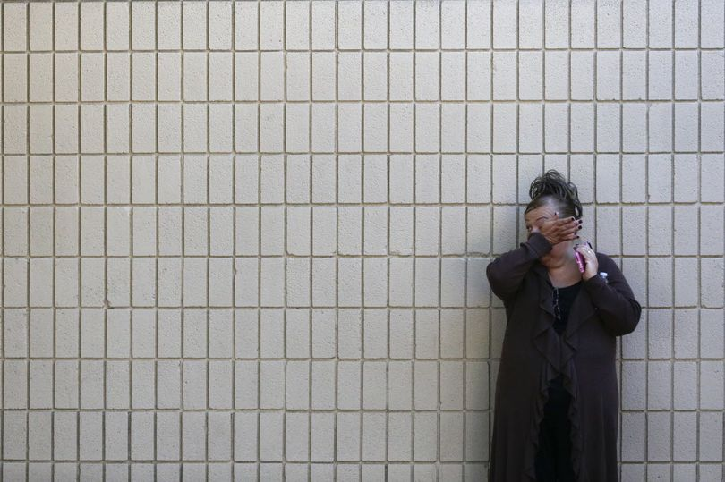 A woman wi[es her tears at a community center where family members are gathering to pick up survivors after a shooting rampage that killed multiple people and wounded others at a social services center in San Bernardino, Calif., today. (AP Photo/Jae C. Hong)