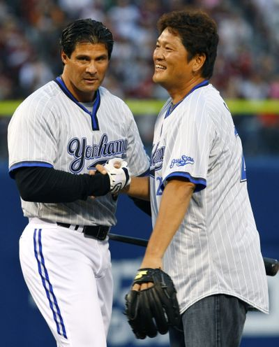 Jose Canseco, left, faced former Mariners closer Kazuhiro Sasaki before a game in Japan on Sunday. (Associated Press / The Spokesman-Review)