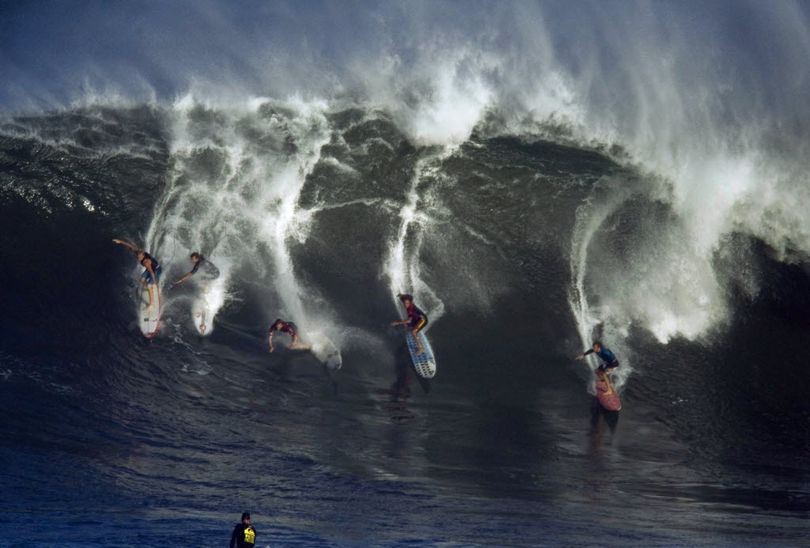 Surfers catch a massive wave, at Waimea Bay on Thursday, Jan. 20, 2011 on Oahu, Hawaii North Shore. Organizers of the big wave surfing contest known as