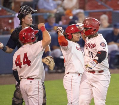 Isaias Quiroz, right, celebrates with Tanner Gardner, left, and Francisco Ventura, center, after he brought them in with a three-run home run against the Everett AquaSox at Avista Stadium on Sept. 6. The Indians Player Development Agreement with the Texas Rangers was renewed by the parent club on Monday. (Jesse Tinsley / The Spokesman-Review)