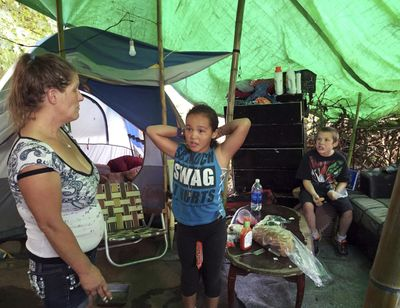 In this Aug. 10, 2016, file photo, Deitra Schmer watches as her granddaughter, Andrea Brown, brushes her hair and grandson Adrian Atkinson, right, looks on in Schmer's tent in a homeless encampment along the Springwater Corridor bike and pedestrian trail in Portland, Ore. In 2015 counters found 3,800 people sleeping on the streets, in shelters or in temporary housing with about 12,000 more squeezed into homes with other families. (Gillian Flaccus / Associated Press)
