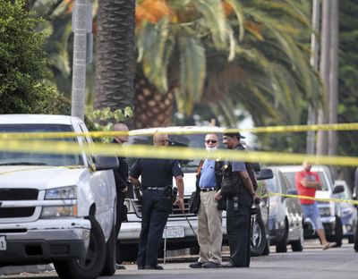 Los Angeles police investigators work the scene of a fatal shooting in a neighborhood west of downtown Los Angeles on Saturday. (Reed Saxon / Associated Press)