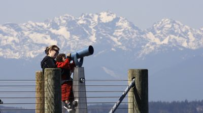 Dawn Bennett Wright holds up her 3-year-old son Gabriel  on Monday to look through a viewing scope toward downtown Seattle, with the Olympic Mountains in the background. Temperatures in Seattle climbed toward 70 degrees Monday, following sun and 60s over the weekend.  (Associated Press / The Spokesman-Review)