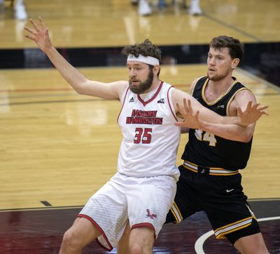 Eastern Washington's Tanner Groves battles for position under the basket against Idaho's Scott Blakney (34) Saturday, Feb. 6, 2021 at Reese Court in Cheney. The EWU Eagles beat the Idaho Vandals 90-64.  (Jesse Tinsley/The Spokesman-Review)