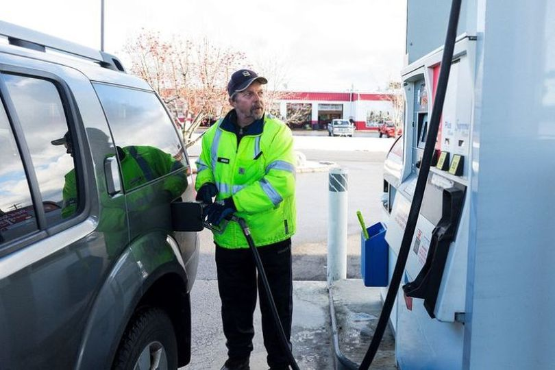 Michael Trautvetter, a service attendant at the Chevron service station on Honeysuckle Avenue in Hayden, finishes pumping gas for a customer Wednesday during his shift. The station is offering full service at no charge during the winter months for the third consecutive year. (Shawn Gust / Coeur d'Alene Press)