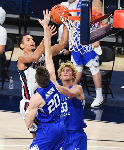 Gonzaga guard Jalen Suggs drives to the basket as Brigham Young's Spencer Johnson and Caleb Lohner defend on Thursday night.  (Colin Mulvany/THE SPOKESMAN-REVIEW)