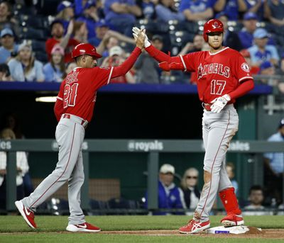 Los Angeles Angels' Shohei Ohtani (17) celebrates with third base coach Dino Ebel (21) after hitting a three-run triple during the seventh inning of a baseball game against the Kansas City Royals Thursday, April 12, 2018, in Kansas City, Mo. (Charlie Riedel / AP)