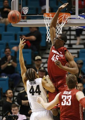 Washington State center Valentine Izundu blocks a shot by Colorado guard Josh Fortune (44) during the second half of an NCAA college basketball game in the first round of the Pac-12 tournament on March 9. (John Locher / Associated Press)