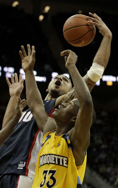 Gonzaga's Robert Sacre, back, grabs a rebound over Marquette's Jimmy Butler. (Associated Press)