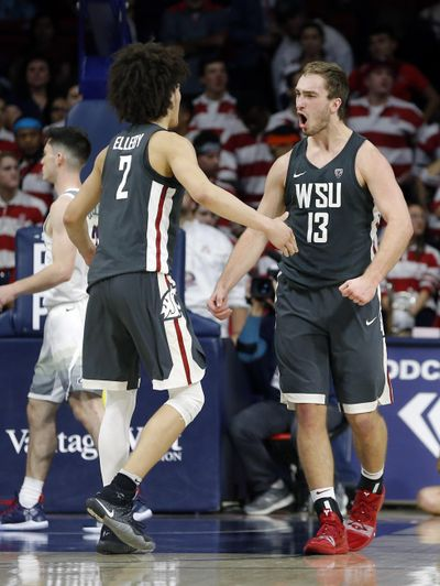 Washington State's CJ Elleby and Jeff Pollard (13) celebrate the team's 69-55 win over Arizona in an NCAA college basketball game Saturday, Feb. 9, 2019, in Tucson, Ariz. (Rick Scuteri / AP)