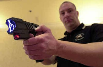 Clay Winn, of Taser International, demonstrates the company's Advanced M-26 model in Las Vegas. Taser International Inc. won a $1.8 million contract to provide stun guns to military personnel, it was announced Wednesday.  (File/Associated Press / The Spokesman-Review)