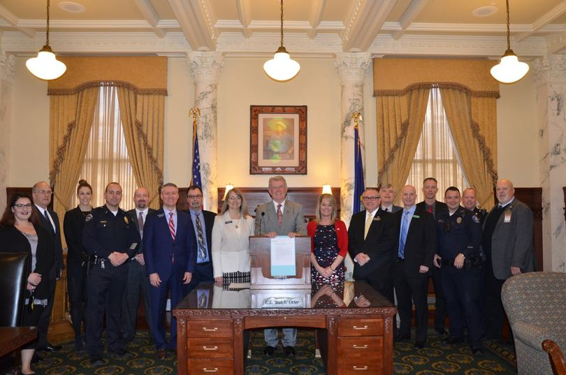Idaho Gov. Butch Otter poses with supporters of HB 665, legislation updating Idaho's school threats law to cover social media and adding felony provisions when a deadly weapon is involved, after he signs it into law in his office on Friday, March 23, 2018. (State of Idaho)
