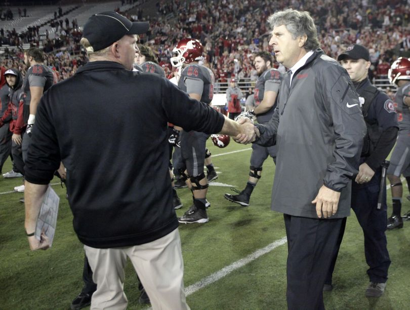 Washington State head coach Mike Leach, right, and Idaho head coach Paul Petrino shake hands in a chilly postgame meeting after the Cougars beat the Vandals 42-0 in 2013. (Dean Hare / Associated Press)