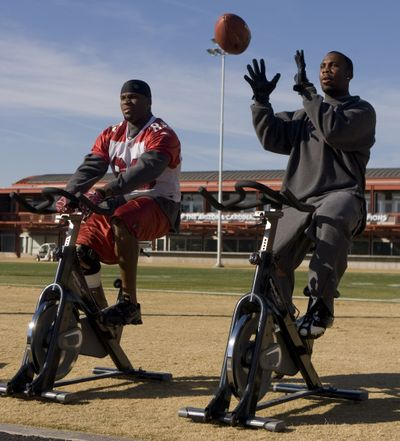 The Arizona Cardinals won't know until game time if they can ride the talents of wide receiver Anquan Boldin, right, in today's playoff game against the Panthers at Charlotte, N.C. Boldin, riding an exercise bike alongside tight end Ben Patrick during football practice in Arizona earlier this week, is trying to overcome a strained left hamstring.  (Associated Press / The Spokesman-Review)