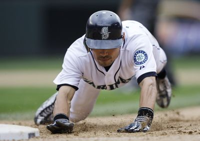 Ichiro Suzuki dives back to first base on a pickoff attempt.  (Associated Press / The Spokesman-Review)