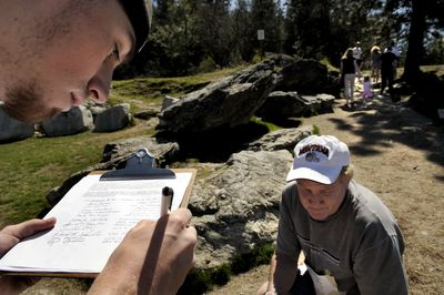 """This is just the first step to privatizing this hill,"" said Coeur d'Alene attorney Steve Bell, right, as Ryan Ghramm, left, of Hayden, signed a petition on Tuesday asking the Coeur d'Alene City Council not to allow commercial  tours of Tubbs Hill.  (Kathy Plonka / The Spokesman-Review)"