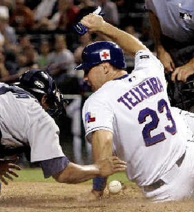 Mark Teixeira knocks the ball from Seattle's Miguel Ojeda to score Rangers' fourth run.   (Associated Press / The Spokesman-Review)