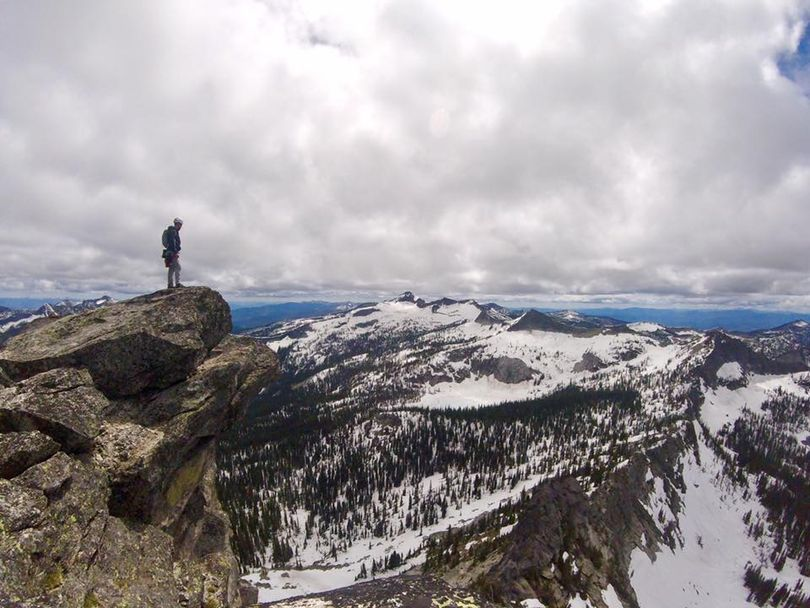 Climber Bryson Williams of Spokane enjoys the view from the top of Harrison Peak looking south along the Selkirk Crest on June 11, 2017.  (Benjamin Read)