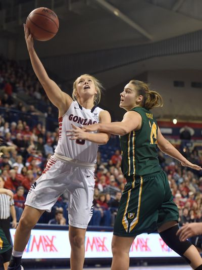 "Gonzaga's Georgia Stirton, left, takes the layup while getting hacked by San Francisco's Michaela Rakova on Dec. 31, 2015. Stirton recalls that ""big school"" basketball was a shock because of how fast the players were. (Jesse Tinsley / The Spokesman-Review)"