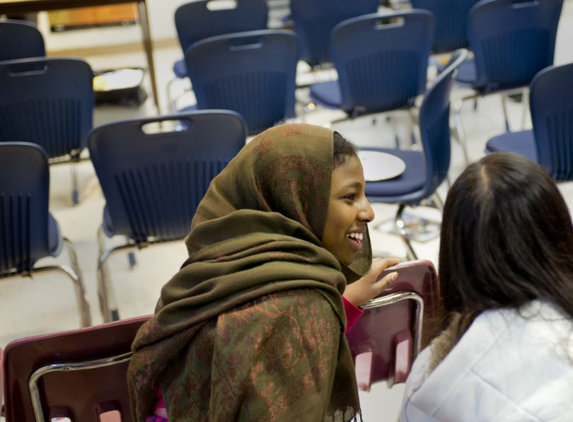 North Pines Middle School eighth-grader Asha Abbas, 14, left, and seventh-grader Isabella Moua, 13, share a laugh Wednesday after an English language development class presentation in which students tell stories about themselves using Microsoft Photo Story. (Tyler Tjomsland)