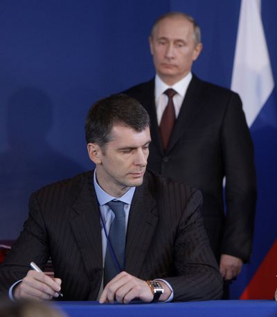 In this 2009 file photo, Russian Prime Minister Vladimir Putin, right, looks on as Mikhail Prokhorov signs an agreement during a Franco-Russian meeting in Rambouillet, France. Prokhorov, one of Russia's richest tycoons and the owner of the New Jersey Nets basketball team, said  he will run against Putin in the March presidential election. (Alexei Druzhinin / Pool Ria Novosti)