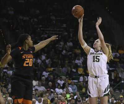 Baylor forward Lauren Cox (15) shoots past Oklahoma State center Mariam Gnanou (15) during Saturday's game. Baylor won 76-44. (Jerry Larson / Associated Press)