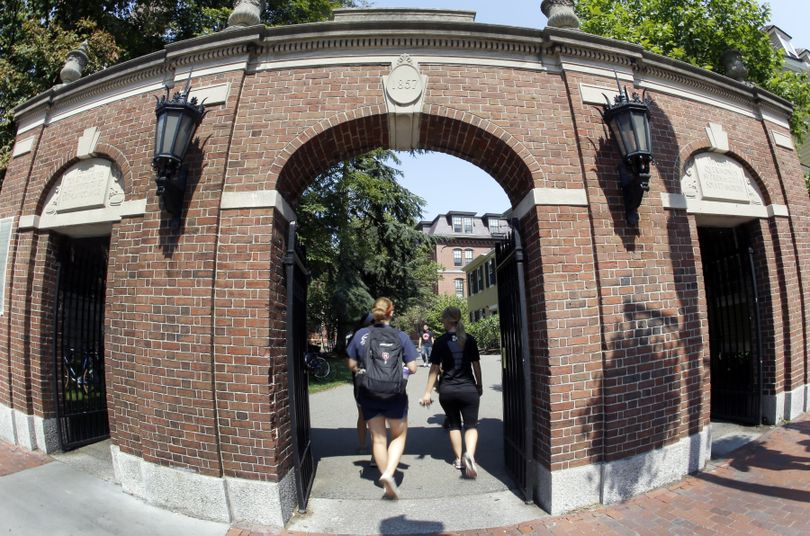 Pedestrians walk through a gate on the campus of Harvard University in Cambridge, Mass. Thursday, Aug. 30, 2012. Dozens of Harvard University students are being investigated for cheating after school officials discovered evidence they may have wrongly shared answers or plagiarized on a final exam. Harvard officials on Thursday didn't release the class subject, the students' names, or specifically how many are being investigated. (Elise Amendola / Associated Press)