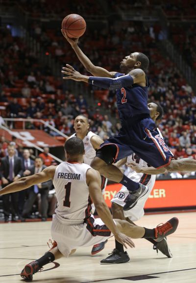 Arizona's Mark Lyons goes to the basket as former EWU Eagle Glen Dean (1) tumbles in second-half action. (Associated Press)