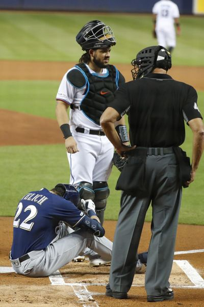 Milwaukee Brewers' Christian Yelich (22) sits on the ground after an injury while at bat as Miami Marlins catcher Jorge Alfaro, rear, and home plate umpire Kerwin Danley look on during the first inning of a baseball game, Tuesday, Sept. 10, 2019, in Miami. (Wilfredo Lee / Associated Press)