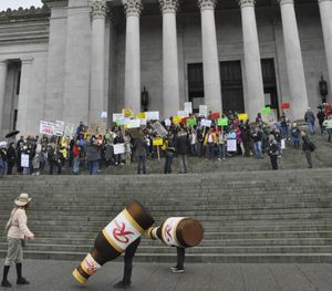 """OLYMPIA -- The Rainier bottles """"graze"""" in front of the Capitol during a protest against extending the state's beer surcharge to microbreweries. (Jim Camden)"""