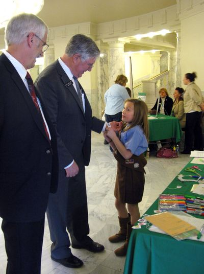 Reps. Ron Mendive, R-Coeur d'Alene, left, and Lance Clow, R-Twin Falls, talk to 9-year-old Brownie Ella Marcum-Hart in the Idaho state Capitol on Monday. Marcum-Hart is attaching a goal-setting bracelet to Clow's wrist. (Betsy Russell)