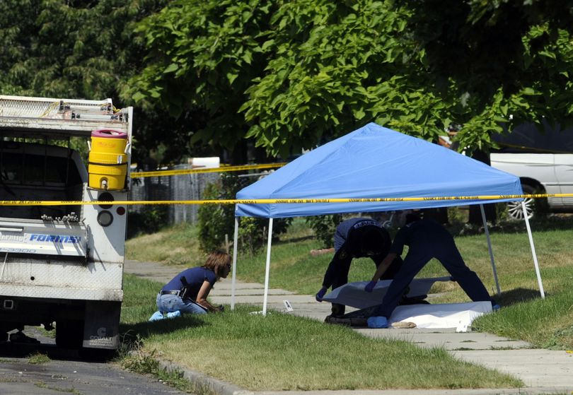 Investigators from the Spokane Police Department and the Spokane County Sheriff's Department examine the scene and cover the body of a man shot by police Friday, July 10, 2009, in north Spokane.   JESSE TINSLEY jesset@spokesman.com (Jesse Tinsley / The Spokesman-Review)