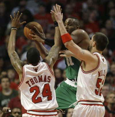 Boston Celtics' Glen Davis, center, passes the ball between Chicago Bulls defenders Tyrus Thomas  and Brad Miller.  (Associated Press / The Spokesman-Review)