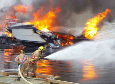 Firefighters battle the fire at the Harborview Marina in Gig Harbor, Wash., Wednesday. Firefighters monitored the smoldering wreckage of a downtown marina Wednesday after an early morning fire burned 50 boats and spewed billowing black smoke. No injuries were reported, fire spokeswoman Penny Hulse said. One person living aboard a boat fled the covered marina before it was charred, she said.   (Associated Press / The Spokesman-Review)