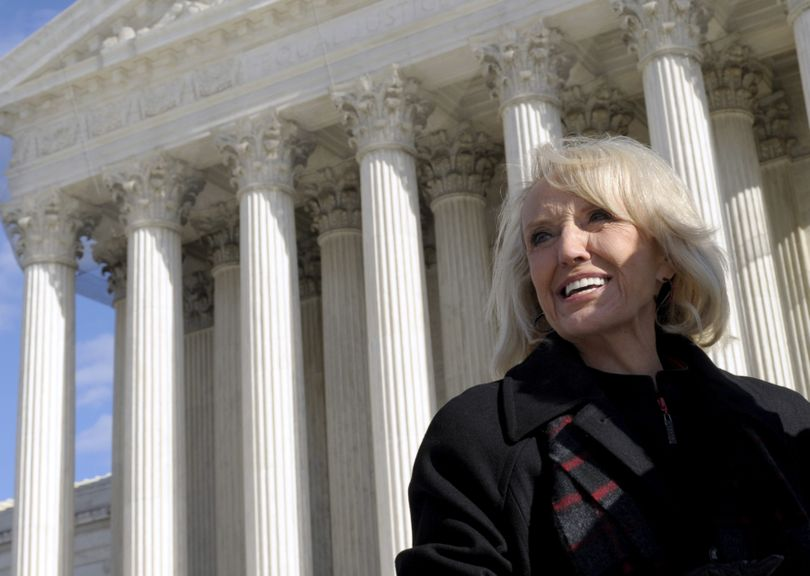 Arizona Gov. Jan Brewer stands outside the Supreme Court in Washington on Wednesday,  after attending arguments  regarding the Arizona employer sanctions law.  (Associated Press)