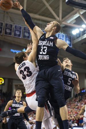 BYU's Nate Austin swats away a shot by Gonzaga's Kyle Wiltjer in the waning seconds on Thursday. (Colin Mulvany / The Spokesman-Review)