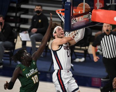 Gonzaga forward Corey Kispert smiles on his way to an easy layup against San Francisco Dons forward Josh Kunen during a Jan. 2 West Coast Conference home game.  (Colin Mulvany/The Spokesman-Review)