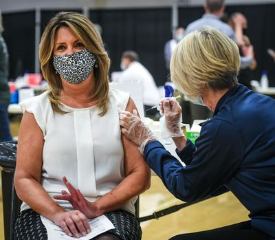 Spokane Mayor Nadine Woodward receives a COVID-19 vaccination from Providence Health Care Chief Operation Officer Peg Currie on April 22 at the Gonzaga University Martin Centre Field House.  (Dan Pelle/THESPOKESMAN-REVIEW)