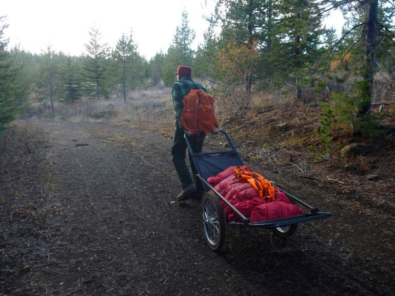 A hunter carts out the boned-out meat of an elk on a national forest road that's been closed to motorized use. (Rich Landers)