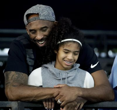 In this July 26, 2018, file photo former Los Angeles Laker Kobe Bryant and his daughter Gianna watch during the U.S. national championships swimming meet in Irvine, Calif. Federal investigators say wreckage from the helicopter that crashed last month and killed Bryant, his daughter and seven others did not show any outward evidence of engine failure, the National Transportation Safety Board said Friday, Feb. 7, 2020. (Chris Carlson / Associated Press)
