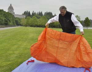 OLYMPIA -- Gov. Jay Inslee practices deploying a fire shelter during an annual exercise in the park below the Capitol at the start of fire season.  (Jim Camden)