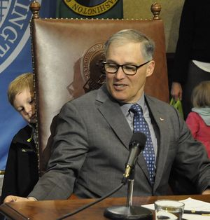 OLYMPIA -- Logan Hargrove, grandson of Sen. Jim Hargrove, D-Hoquiam, peers around the corner of the governor's chair as Jay Inslee prepares to sign his grandfather's last bill before retiring from the Legislature. (Jim Camden/The Spokesman-Review)