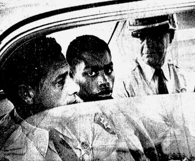 In this February 1964 file photo, Henry Montgomery, flanked by two deputies, awaits the verdict in his trial for the murder of Deputy Sheriff Charles H. Hurt in Louisiana. (John Boss / Associated Press)